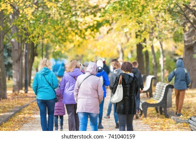 Crowd of people walking in the autumn city park