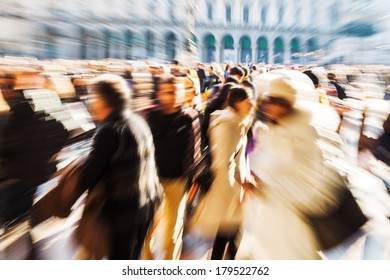 crowd of people walking on a city square in motion blur and zoom effect