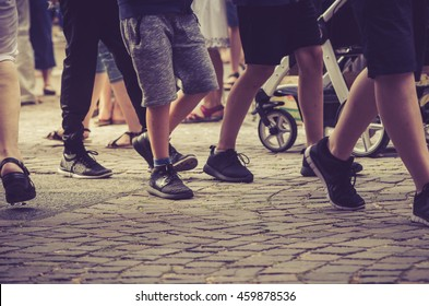 Crowd of people walking on cobblestone pedestrian zone - Detail of legs and shoes