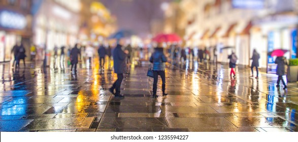 crowd of people walking on the night and rainy streets in the city