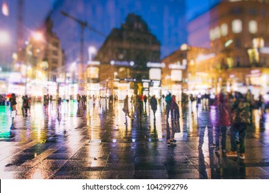 crowd of people walking on rainy city streets by night
