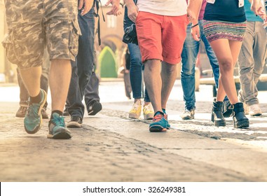 Crowd of people walking on the street - Detail of legs and shoes moving on sidewalk in city center - Travelers with multicolor clothes on vintage filter - Shallow depth of field with sunflare filter