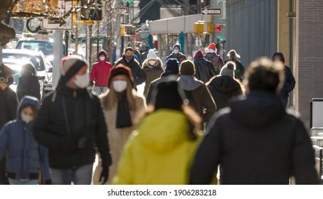 Menschenmenge, die mit Masken auf der Straße spaziert