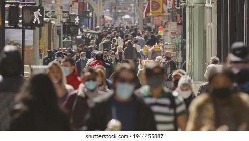 Crowd of people walking street wearing masks during Covid 19 pandemic