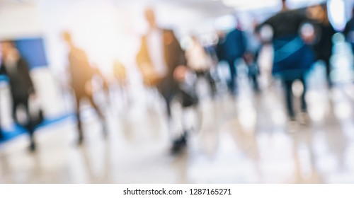 crowd of people walking at a trade show Intentionally blurred background
