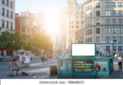 Crowd of people walking in Union Square Park near the 14th street subway station in Manhattan, New York City NYC with a blank billboard sign and glowing sunlight in the background