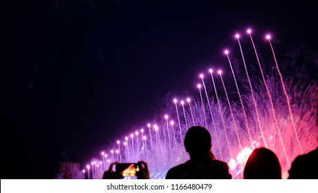 Crowd of people watching fireworks and taking a salute to the smartphone. Beautiful bright pyrotechnic show
