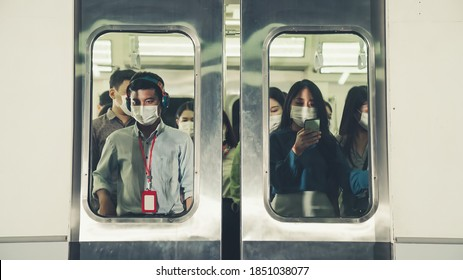Crowd of people wearing face mask on a crowded public subway train travel . Coronavirus disease or COVID 19 pandemic outbreak and urban lifestyle problem in rush hour concept .
