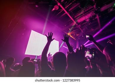 Сenter of crowd raise their hands up at  concert on DJ set at nightclub