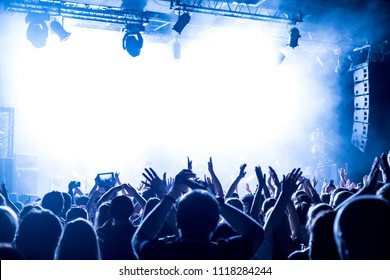 crowd with raised nands during concert at nightclub
