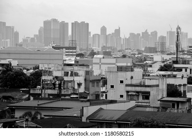 A crowd of residential houses in Quezon City Philippines with the skyline of buildings at the backdrop. Photo in black and white.