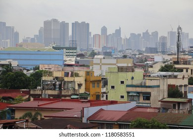 A crowd of residential houses in Quezon City Philippines with the skyline of high rise buildings at the backdrop.