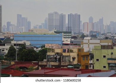 A crowd of residential houses in Quezon City Philippines with the skyline of high rise buildings at the backdrop. Photo taken during an overcast day.