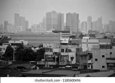 A crowd of residential houses in Quezon City Philippines with the skyline of high rise buildings at the backdrop. Black and white photo taken during an overcast day.