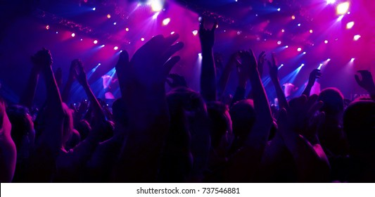 A crowd of spectators at a concert applauded their hands up. People in the red ramps. Stage lights at a concert of different colors. Raspberry and blue spotlights
