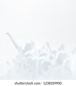 Crowd of spectators at a concert in light blue tonality. High key background with a people on an open playground at a concert. Abstract soft focus image with copy space