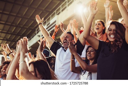 Crowd of sports fans cheering during a match in stadium. Excited people standing with their arms raised, clapping and yelling to encourage their team.