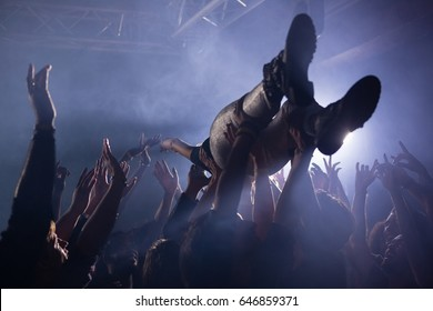 Crowd surfing at a concert in nightclub