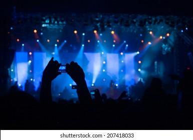 Crowd taking photos of their favourite band at a concert with fabulous blue stage lights
