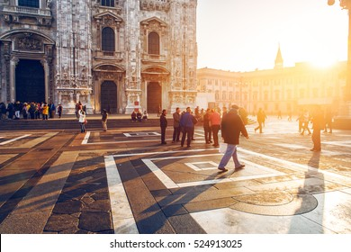crowd of tourist people walking in center of old town near Duomo in Milan, Italy at sunset time