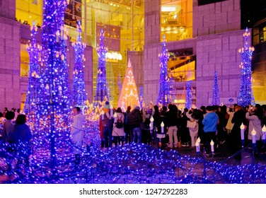 A crowd of tourists admiring and taking photos of the romantic Winter Illumination Display with decorated Christmas trees and dazzling lights in a pedestrian square in Caretta Shiodome, Tokyo, Japan