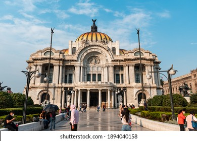Crowd of travelers standing on path near famous Palacio de Bellas Artes against cloudy blue sky on sunny day during pandemic in Mexico City, December 12, 2020
