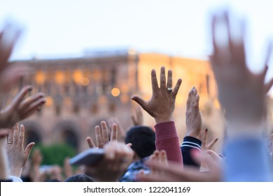 Crowd of united people hands up in the city center.