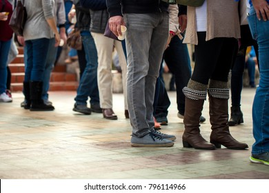Crowd of unrecognizable people wait in line in a urban setting/queue of people