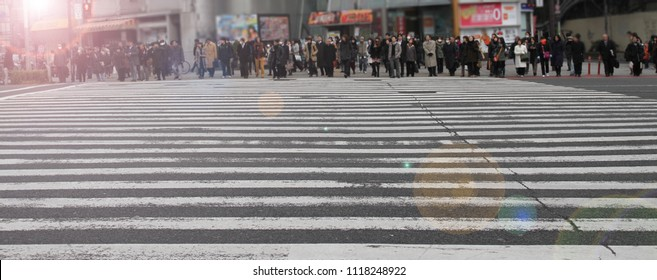 A crowd of unrecognizable people are waiting to cross at a big intersection in Ginza, Tokyo, Japan.  Intersection with group of people crossing.
