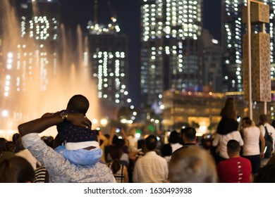 Crowd of visitors contemplating the show around the dancing fountains at night outside the Dubai Mall in the United Arab Emirates.