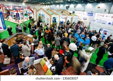 Crowd of visitors network during an event at Ecobuild at Excel in London, UK on March 6, 2013. Business people and visitors walk and visit crowded exhibitor stands and booth at sustainable trade fair