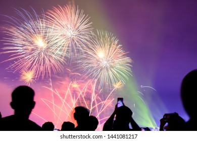 Crowd watching fireworks and celebrating city founded. Beautiful colorful fireworks display in the urban for celebration on dark night background.