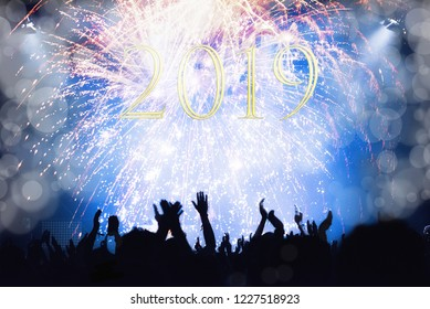 Crowd watching New Year fireworks and celebrating. 2019 written with yellow numbers