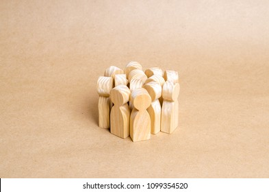 A crowd of wooden figures of people stands in a pile on a beige paper background. The concept of cohesion and cooperation. Frightened people, herd behavior. Team, target audience