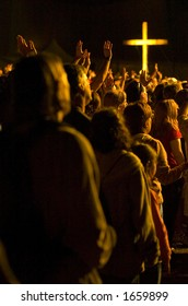 A crowd worships with illuminated cross