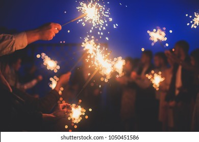 A crowd of young happy people with sparklers in their hands during birthday celebration