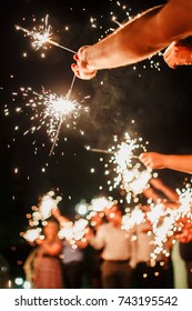 A crowd of young happy people with sparklers in their hands during celebration. Sparkler in hands on a wedding - bride, groom and guests holding lights in hand. Sparkling lights of bengal fires.
