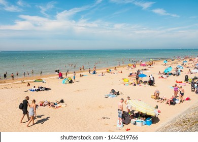 Crowded beach in Cabourg, Normandy, France. Beautiful sunny summer day on the coast, wide-angle shot. Cleard water at high tide. July 2019. Blue sky and clouds.