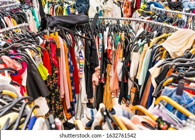 Crowded clearance section in a clothing store, with various colorful garments placed tightly on racks in no particular order; fast fashion concept
