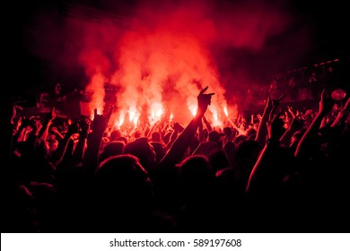 Crowded dance floor in nightclub. Big live music show in club. People get wild on concert. Big crowd on festival. Fans burn prohibited fire works. Dangerous red fireworks in crowd.