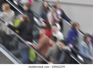 Crowded shoppers on escalator in shopping mall. Blur added for effect.