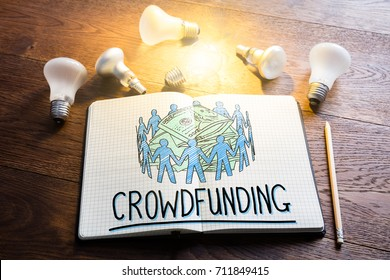 Crowdfunding Concept In Notepad Near Glowing Lightbulbs