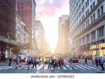Crowds of diverse people cross the busy intersection on 23rd Street and 5th Avenue in Manhattan with rush hour traffic in the background
