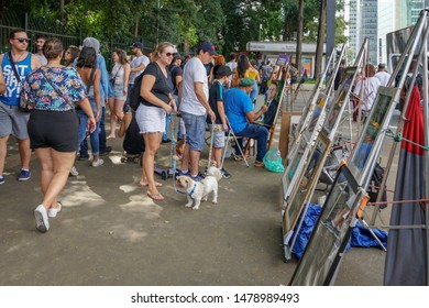 Crowds looking at painting in Paulista Avenue on Sunday afternoon. Paulista Avenue is closed for vehicles every Sunday. Sao Paulo, Brazil. 02/24/2019