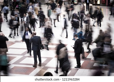 Crowds of motion blurred people moving in busy city scene