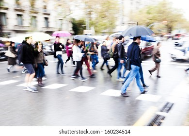 crowds of people crossing the street on a rainy day in the city