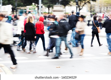 crowds of people in motion blur crossing the street