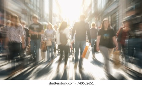 crowds of people in motion blur crossing a city street at sunset