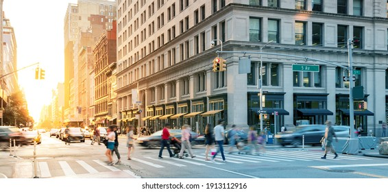 Crowds of people in motion walking across the busy intersection on 5th Avenue in Midtown Manhattan, New York City NYC