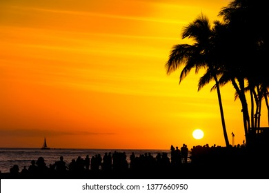 Crowds of tourists gather to watch an orange sunset on Waikiki Beach Honolulu Oahu Hawaii USA